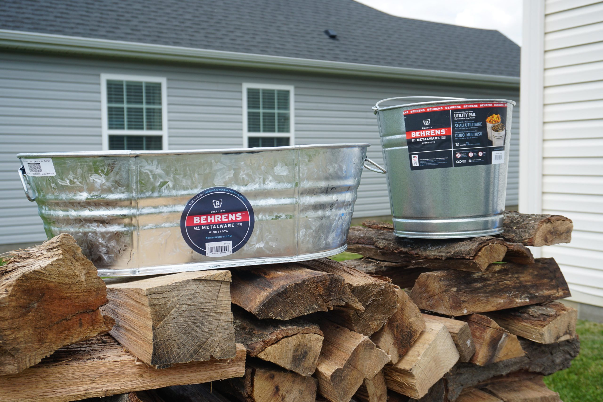 Behren's Metal Buckets sitting on top of firewood