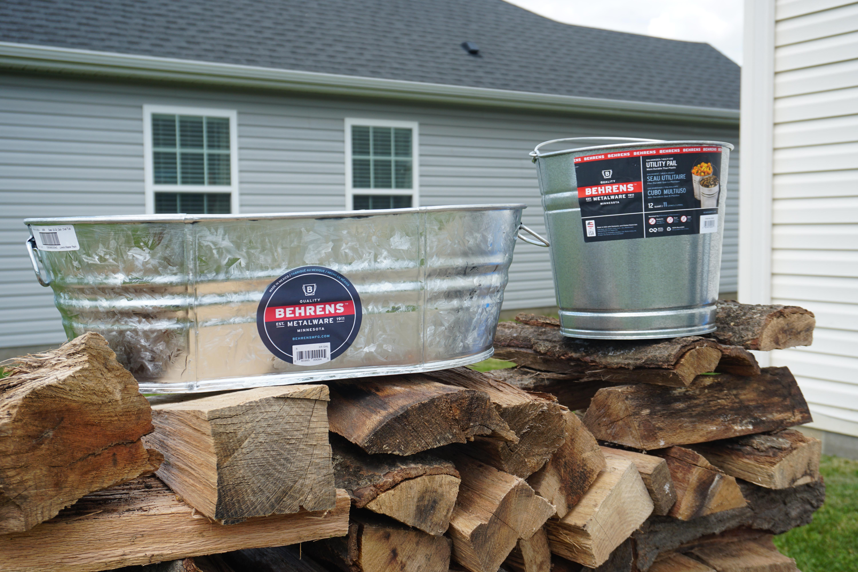 Behren's Metal Buckets sitting on top of firewood