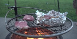 Breeo grilling steaks and potatoes