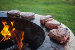 Breeo X-Series Smokeless fire pit steaks and burgers on sear plate